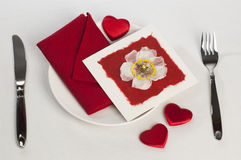 Table setting of Valentine's Day. With greeting card with flower and small hearts on white tablecloth stock images