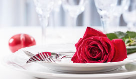 Table setting for valentines or wedding day with red roses. Romantic table setting for two with roses plates cups and cutlery.  Stock Photography