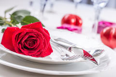Table setting for valentines or wedding day with red roses. Romantic table setting for two with roses plates cups and cutlery.  Stock Photo