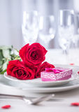 Table setting for valentines or wedding day with red roses. Romantic table setting for two with roses plates cups and cutlery.  Stock Images