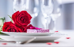 Table setting for valentines or wedding day with red roses. Romantic table setting for two with roses plates cups and cutlery.  Stock Photos