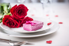Table setting for valentines or wedding day with red roses. Romantic table setting for two with roses plates cups and cutlery.  Royalty Free Stock Image