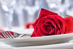 Table setting for valentines or wedding day with red roses. Romantic table setting for two with roses plates cups and cutlery.  Royalty Free Stock Photography