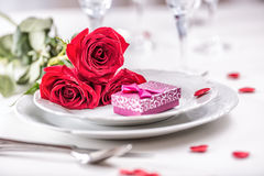 Table setting for valentines or wedding day with red roses. Romantic table setting for two with roses plates cups and cutlery.  Royalty Free Stock Photo
