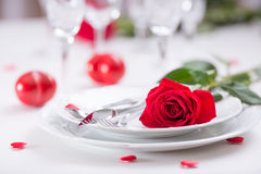 Table setting for valentines or wedding day with red roses. Romantic table setting for two with roses plates cups and cutlery.  Stock Image