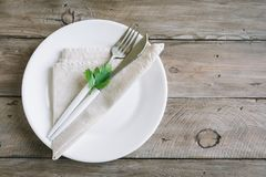 Table setting with green leaf. Table setting with white plate, modern cutlery fork and knife and little leaf of fresh parsley on wooden background, top view Royalty Free Stock Image