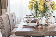 Table setting on wooden dinning room with vase of flower Stock Image