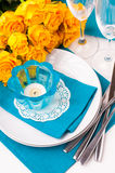 Table setting with yellow roses. Festive table setting with yellow roses, glasses, candles, napkins and cutlery in blue and yellow colors Royalty Free Stock Photos