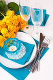 Table setting with yellow roses. Festive table setting with yellow roses, glasses, candles, napkins and cutlery in blue and yellow colors Stock Image