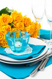 Table setting with yellow roses. Festive table setting with yellow roses, glasses, candles, napkins and cutlery in blue and yellow colors Stock Images