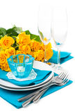 Table setting with yellow roses. Festive table setting with yellow roses, glasses, candles, napkins and cutlery in blue and yellow colors Royalty Free Stock Photography