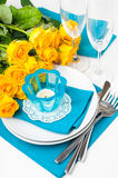 Table setting with yellow roses. Festive table setting with yellow roses, glasses, candles, napkins and cutlery in blue and yellow colors Royalty Free Stock Image