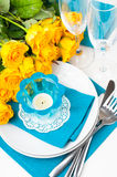 Table setting with yellow roses. Festive table setting with yellow roses, glasses, candles, napkins and cutlery in blue and yellow colors Royalty Free Stock Images