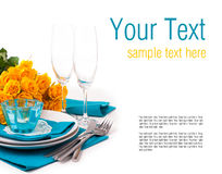 Table setting with yellow roses, ready template. Festive table setting with yellow roses, glasses, candles, napkins and cutlery in blue and yellow colors, ready Royalty Free Stock Photography