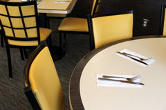 Table settings and soft yellow chairs at diner Stock Images