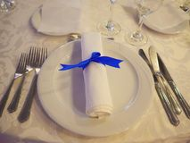 Table setup with silverware placed in the order of use, napkin and white china royalty free stock image