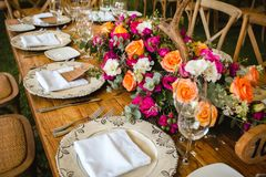 Table setup, wedding guest table, reception layout in pantone living coral and deer horns rustic style. Wine glasses stock photos