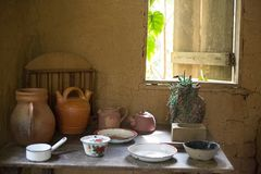 A table with several decorated old objects. The wall is made of clay is royalty free stock photos