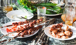 Table with shish kebabs and vegetables Royalty Free Stock Photography