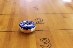 Table Shuffleboard Puck. Close-up shot of a puck weight on an indoor shuffleboard table Stock Images