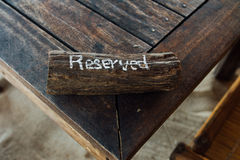 Table with sign reserved on wooden plank. Reservation table in restaurant Stock Image