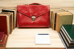Table for signing documents. On a wooden table books, documents, red briefcase Stock Images