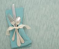 Table Silverware Place Setting in Teal Colors with mat and cloth napkin Royalty Free Stock Image