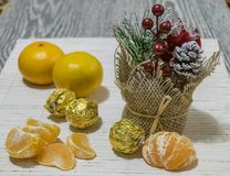 On the table are slices of mandarin, candy and Christmas decoration. stock photos