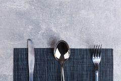 On the table is a spoon, fork and knife on a serving napkin. Stock Images