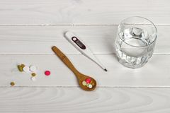 Table spoon with tablets, thermometer and glass of water on white wooden table. Medical concept.  Royalty Free Stock Photo