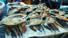 Table stand placed with brown dried fish ready to be sold by the sales woman to make a living at the market place in Flores. Stock Photo