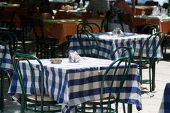 Table in a street cafe. Empty table with chairs in a street cafe covered by blanket stock images