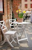 Table of a street cafe with yellow jonquils Royalty Free Stock Photo