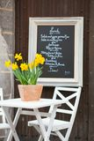Table of a street cafe with yellow jonquils Royalty Free Stock Image