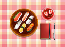 A table with sushi, a cocktail drink, a ballpen and a notebook Stock Photos