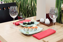 Table with sushi at plates and empty glasses Royalty Free Stock Photos