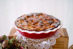 Table with sweet pie in red porcelain tray laid on wooden box Royalty Free Stock Image