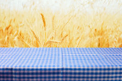 Table with tablecloth over wheat field background Royalty Free Stock Photo