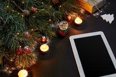 Table with tablet computer, christmas toys, stars and fluffy fir branches. Free space for text. Top view. Copy space. Close-up Royalty Free Stock Photo