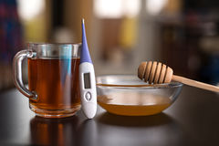 On the table are tea, thermometer, tablets and honey. On the table are cold remedies: Tea, thermometer, tablets and honey Royalty Free Stock Photos