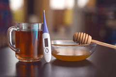 On the table are tea, thermometer, tablets and honey. On the table are cold remedies: Tea, thermometer, tablets and honey Stock Photos