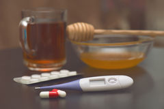 On the table are tea, thermometer, tablets and honey. On the table are cold remedies: Tea, thermometer, tablets and honey royalty free stock image