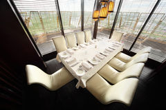 Table and ten white chairs in empty restaurant Stock Photos