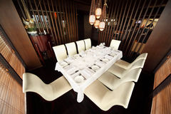 Table and ten white chairs in empty restaurant Royalty Free Stock Photography