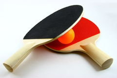 Table Tennis. An orange Ping Pong (table tennis) ball between two bats royalty free stock photos