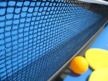 table-tennis-ball-and-racket-against-net Royalty Free Stock Photos