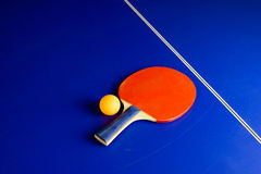 Table Tennis Ball and a Racket on a Blue Table Royalty Free Stock Image