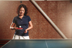 Table tennis, female player with racket hits ball Stock Image