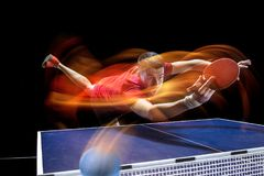 The table tennis player serving. The table tennis player in motion. Fit young sports man tennis-player in play on black background with lights. Movement, sport Royalty Free Stock Photo