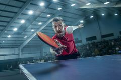 The table tennis player serving. The table tennis player in motion. Fit young sports man tennis-player in play on sport arena background with lights. Movement Royalty Free Stock Photography